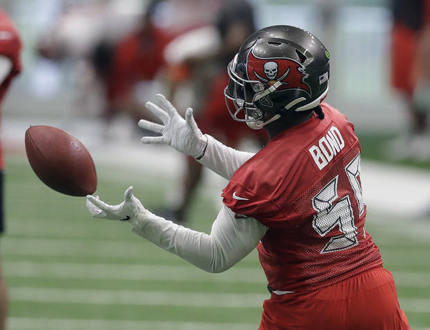 Tampa Bay Buccaneers linebacker Devante Bond reaches for a pass during practice at the NFL football team's training facility Tuesday, May 14, 2019, in Tampa, Fla. (AP Photo/Chris O'Meara)