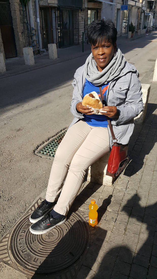 Religion Editor Carla Hinton enjoys a falafel sandwich and orange soda outside an eatery in Israel. [Photo by Carla Hinton, The Oklahoman]