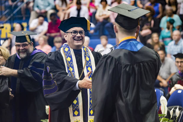 Southeastern Oklahoma State University President Sean Burrage congratulates a graduate during one of two commencement ceremonies in May at Bloomer Sullivan Arena. [Photo Provided]