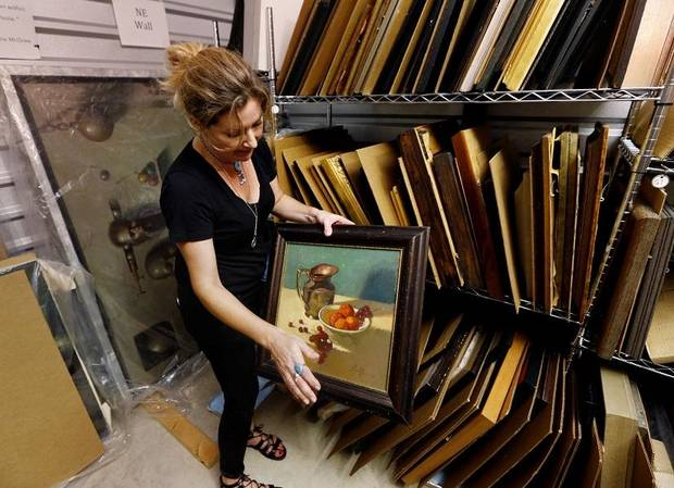 Nicole Poole sorts through art created by her father the late O. Gail Poole in a storage unit on Tuesday, July 5, 2016, in Norman, Okla. [The Oklahoman Archives photo]