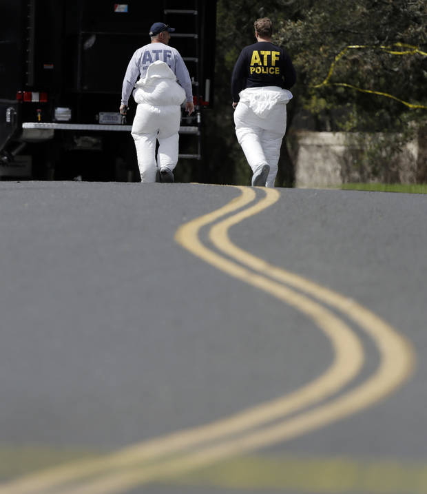 Federal investigators work near the site of Sunday's explosion, Monday, March 19, 2018, in Austin, Texas. Multiple people were injured in the explosion Sunday night, and police warned nearby residents to remain indoors overnight as investigators looked for possible links to other package bombings elsewhere in the city this month. (AP Photo/Eric Gay)