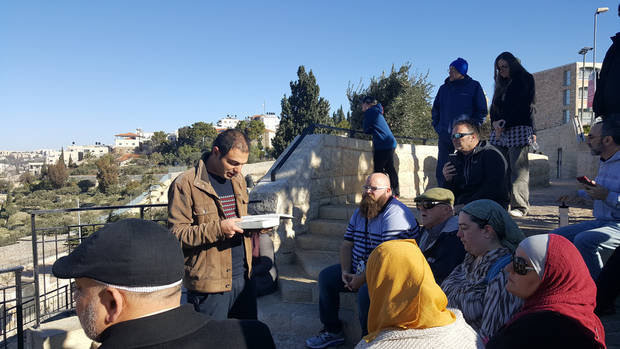 Mejdi Tours guide Adam Nerk reads a biblical passage during the Oklahoma Religions United group's visit to the Mount of Olives on a tour of Israel in January. [Photo by Carla Hinton, The Oklahoman]