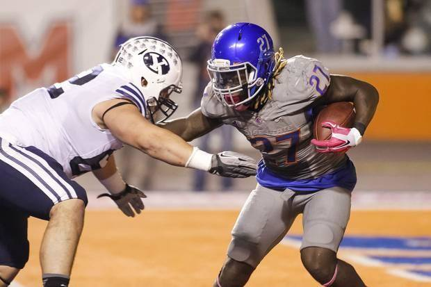 Boise State running back Jay Ajayi (27) runs the ball against BYU defensive linesman Logan Taele during a game last season. (AP Photo)