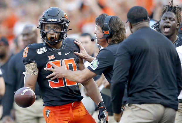 Oklahoma State head coach Mike Gundy reacts to a big gain by Chuba Hubbard (30) in the first quarter during the college football game between the Oklahoma State Cowboys and the Kansas State Wildcats at Boone Pickens Stadium in Stillwater, Okla., Friday, Sept. 27, 2019. [Sarah Phipps/The Oklahoman]