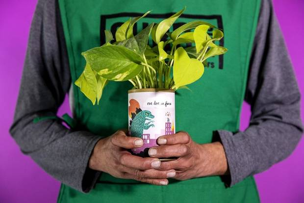 John holds a plant at Curbside Flowers, a new full-service flower shop that is a program of the Homeless Alliance. Every bouquet is made by a Curbside vendor, providing meaningful employment to someone transitioning out of homelessness. [Photo provided by Nathan Poppe]