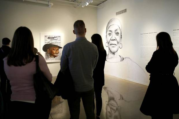"People looks at large-scale wheatpaste drawings in the exhibit ""Tatyana Fazlalizadeh: Oklahoma Is Black,"" a depiction and celebration of Oklahoma City's rich black history, on Feb. 21 at Oklahoma Contemporary in Oklahoma City. [Bryan Terry/The Oklahoman]"