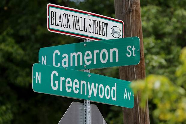 Street signs in the historic Greenwood District in North Tulsa, known at the time as the Black Wall Street, the site of a massacre of African Americans by a white mob, resulting in hundreds of deaths in 1921, are photographed in Tulsa Friday, June 12, 2020. [Doug Hoke/The Oklahoman Archives]