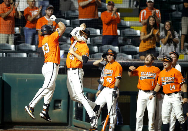 Oklahoma State's Trevor Boone (33) celebrates with Joe Lienhard (46) after hitting a home run in the sixth inning of a Big 12 baseball tournament game between Oklahoma State University (OSU) and TCU at Chickasaw Bricktown Ballpark in Oklahoma City, Okla., Wednesday, May 22, 2019. [Bryan Terry/The Oklahoman]
