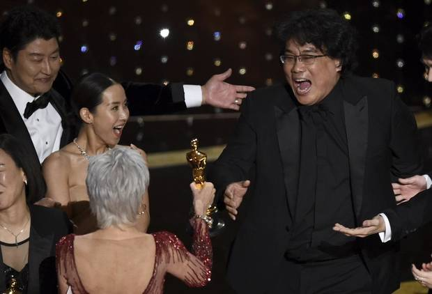"Bong Joon Ho, right, reacts as he is presented with the award for best picture for ""Parasite"" from presenter Jane Fonda at the Oscars on Sunday, Feb. 9, 2020, at the Dolby Theatre in Los Angeles. Looking on from left are Song Kang-Ho and Kwak Sin Ae. [AP Photo/Chris Pizzello]"