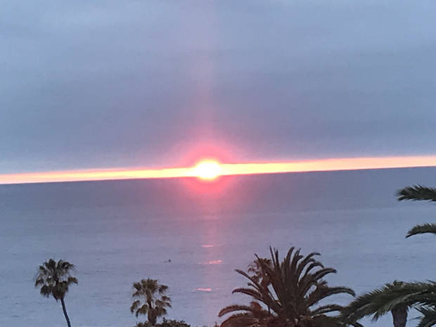 The sun sets between the Pacific Ocean and the cloud cover on the horizon. (Photo by Susy Calonkey)