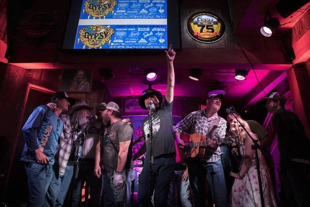 John Cooper, of the Red Dirt Rangers, center, raises his fist in the air at Eskimo Joe's in Stillwater during the finale of the 2018 Bob Childers' Gypsy Cafe songwriters festival. [Photo by Nathan Poppe]