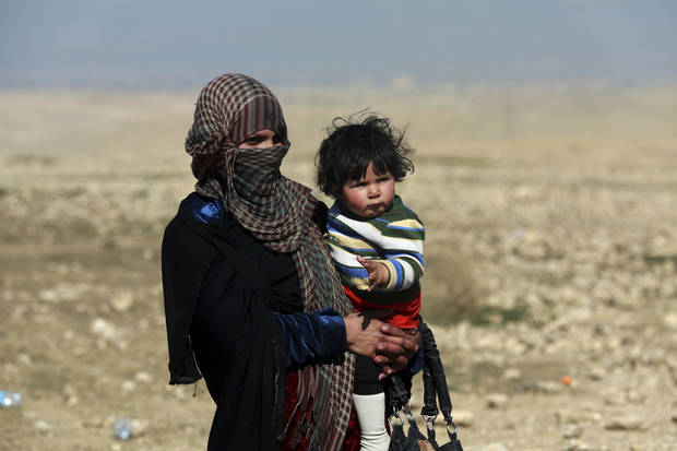 A displaced Iraqi mother and her child flee their home due to fighting between Iraqi special forces and Islamic State militants, on the western side of Mosul, Iraq, Thursday, Feb. 2017. The advance comes as part of a major assault that started five days earlier to drive Islamic State militants from the western half of Mosul, Iraq's second-largest city. (AP Photo/ Khalid Mohammed)