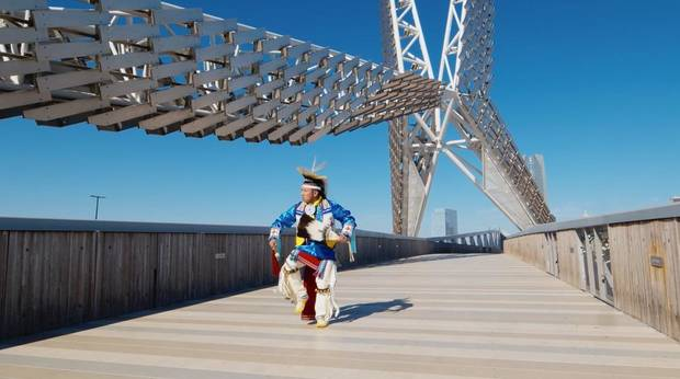 "Sgt. Denny MedicineBird, a Cheyenne & Arapaho and Kiow dancer from Jones, dances across the Skydance Bridge as part of the ""Celebrating America"" primetime inaugural special that aired Wednesday. [Photo provided]"