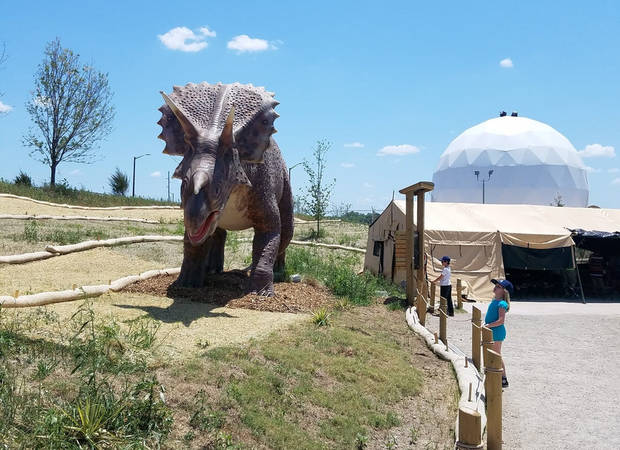 Brenna McDonnell, 8-year-old daughter of Features Writer Brandy McDonnell, looks at a life-sized Triceratops at Field Station: Dinosaurs in Derby, Kansas. [Photo by Brandy McDonnell, The Oklahoman]