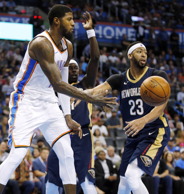 Oklahoma City's Paul George (13) passes away from New Orleans' Anthony Davis (23) and Jrue Holiday (11) in the second quarter during a preseason NBA basketball game between the Oklahoma City Thunder and the New Orleans Pelicans at Chesapeake Energy Arena in Oklahoma City, Friday, Oct. 6, 2017. Photo by Nate Billings, The Oklahoman