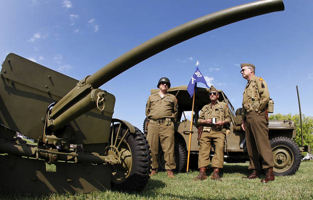 A group of docents at the 45th Infantry Division Museum dressed in authentic World war II uniforms lean against a 1942 Jeep manufactured by Ford Motor Co. In foreground is a 1941 37mm anti-tank gun that was fired to begin the day's activities during the Memorial Day observance in Oklahoma City, Monday, May 31, 2010. Photo by Jim Beckel, The Oklahoman