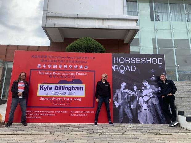 From left, Brent Saulsbury, Kyle Dillingham and Peter Markes of the Oklahoma band Kyle Dillingham & Horseshoe Road pose in front of a billboard for their tour of China. [Photo provided]