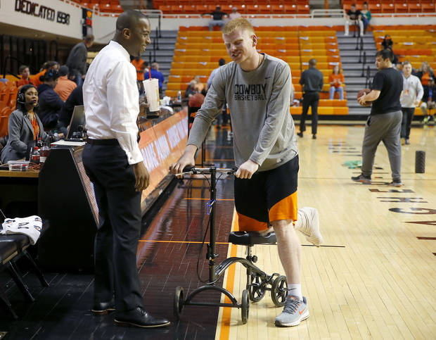 OSU coach Mike Boynton talks with Trey Reeves, who is out for the season with a broken foot, before Wednesday's game against Texas Tech. [Bryan Terry/The Oklahoman]