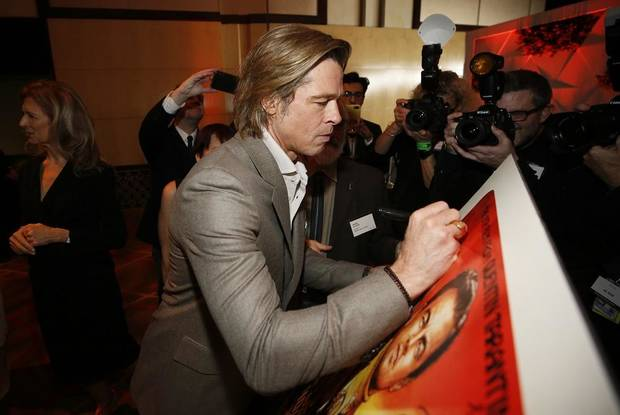 Brad Pitt signs a poster at the 92nd Academy Awards Nominees Luncheon at the Loews Hotel on Monday, Jan. 27, 2020, in Los Angeles. [Photo by Danny Moloshok/Invision/AP]