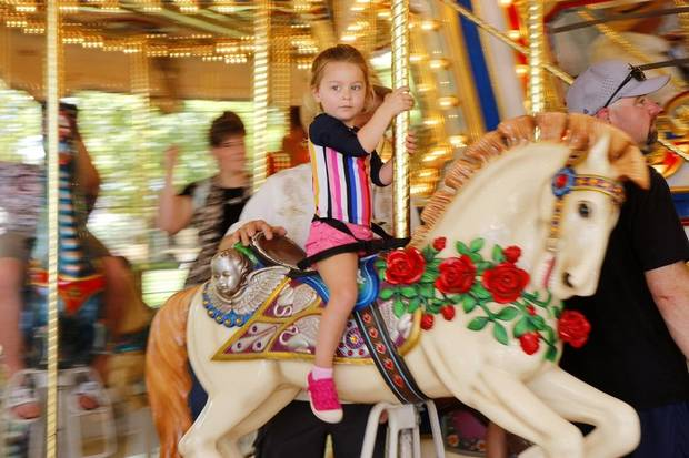 A children rides Mo's Carousel in the Myriad Botanical Gardens during the 2019 Children's Garden Festival. [Doug Hoke photo]