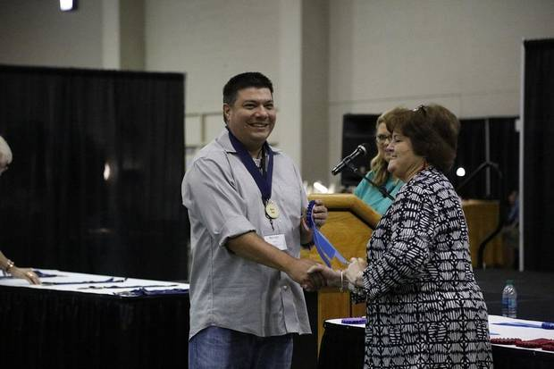 Chase KahWinHut Earles receives his first-place ribbon for contemporary pottery from Red Earth Board President Lona Barrick during the 2019 Red Earth Festival at the Cox Convention Center in Oklahoma City, Oklahoma Friday, June 7, 2019. [Paxson Haws/The Oklahoman]