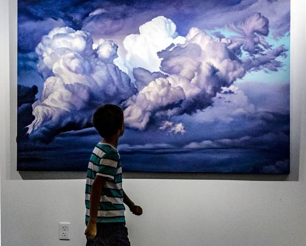 "A child walks past David Holland's painting ""The Gravity of Souls,"" on display in Holland's ""Capturing Clouds"" exhibit at the Visitor Center Lobby of the Crystal Bridge in Oklahoma City, Okla. on Monday, July 29, 2019. [Chris Landsberger/The Oklahoman]"