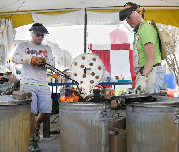Hector Cobos Leon places a piece of pottery in a reduction chamber next to Collin Rosebrook, owner of Paseo Pottery, at Pottery Place during the Festival of the Arts in downtown Oklahoma City, Thursday, April 26, 2018. Pottery Place has been run at the festival for more than 30 years by Paseo Pottery Gallery and Studio. [Nate Billings/The Oklahoman Archives]
