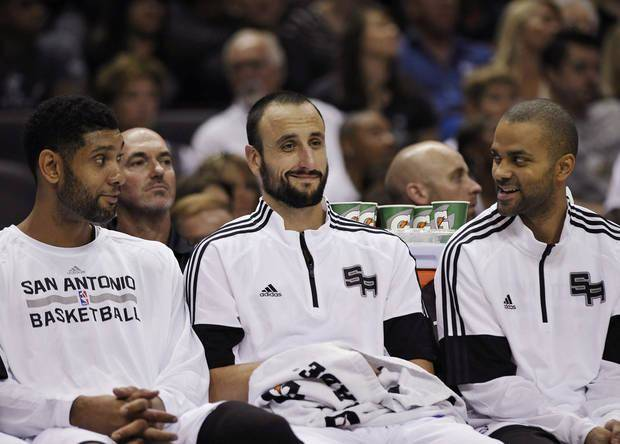 San Antonio Spurs' Tim Duncan; Manu Ginobili, of Argentina; and Tony Parker, of France, talk on the bench during the first half of a preseason NBA basketball game against the Miami Heat, Saturday, Oct. 18, 2014, in San Antonio. Miami won 111-108 in overtime. (AP Photo/Darren Abate)