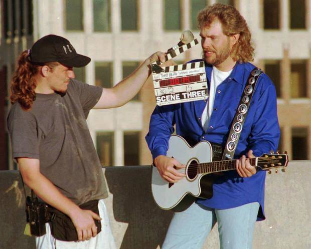 In this 1990s photo, Eric Marshall and Toby Keith appear during the filming of one of Keith's music videos on top of a downtown Oklahoma parking garage last September. [Oklahoman Archives photo]