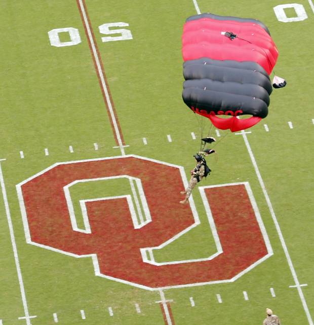 The U.S. Army Special Operations Command Parachute Demonstration Team, the Army Black Daggers, parachutes into the stadium before Saturday's game. The Black Daggers delivered the game ball. [PHOTO BY STEVE SISNEY, The Oklahoman]