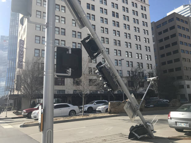 The top section of a traffic light bent backwards from strong winds Wednesday afternoon near Sheridan and Robinson avenues. [Josh Wallace/The Oklahoman]