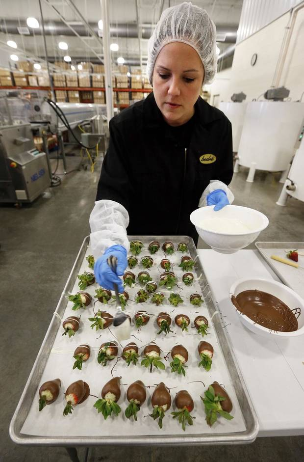 Melissa Walker drizzles white chocolate on chocolate-covered strawberries at Bedre Fine Chocolate on Friday, Feb. 6, 2015 in Davis, Okla. [The Oklahoman Archives]