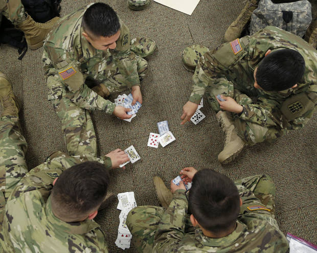 Soldiers pass their time with a game of cards Monday as they and other soldiers from Fort Sill gather at Will Rogers World Airport in Oklahoma City on their way home for Christmas. [Photo by Paul Hellstern, The Oklahoman]