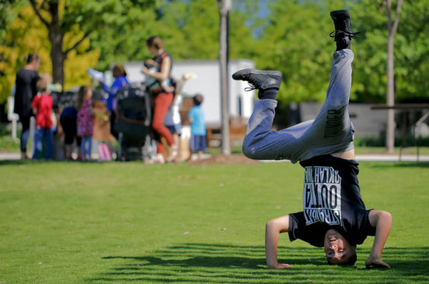 Johnathan Sosa, 12, does a headstand while playing on the Great Lawn during the Myriad Botanical Gardens Earth Day celebration in Oklahoma City, Okla. on Friday, April 22, 2016..  Photo by Chris Landsberger, The Oklahoman