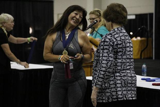 Rosemary Hill, left, receives the Dana and Terry Brown Award for Best of Show from Red Earth Board President Lona Barrick of the 2019 Red Earth Festival at the Cox Convention Center in Oklahoma City, Oklahoma Friday, June 7, 2019. [Paxson Haws/The Oklahoman]
