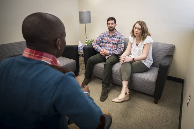 OBU MFT students Scott Pfister (seated on couch, left) and Hannah Mire visit with fellow student Ronald Assimwe (left) in one of the therapy rooms inside OBU's new Marriage and Family Therapy Clinic. Photo provided by OBU.