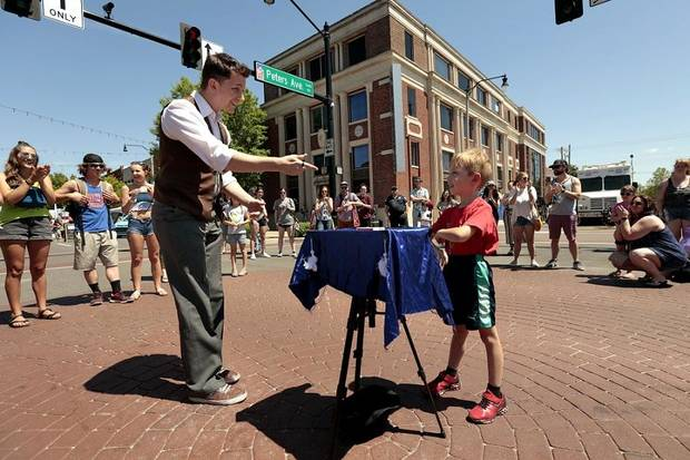 Magician Joe Coover performs a magic show in the street with the aid of volunteer Sawyer Martin, 6, during Norman Music Festival 2019 on April 27, 2019 in Norman, Okla. [Steve Sisney/For The Oklahoman]