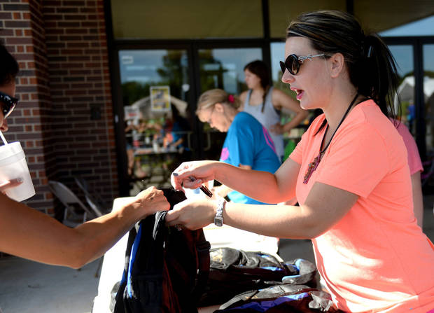 Crystal Coats hands out free school supplies at Family of Faith Church is Choctaw on Saturday Aug 8, 2015. Jackie Dobson/ The Oklahoman