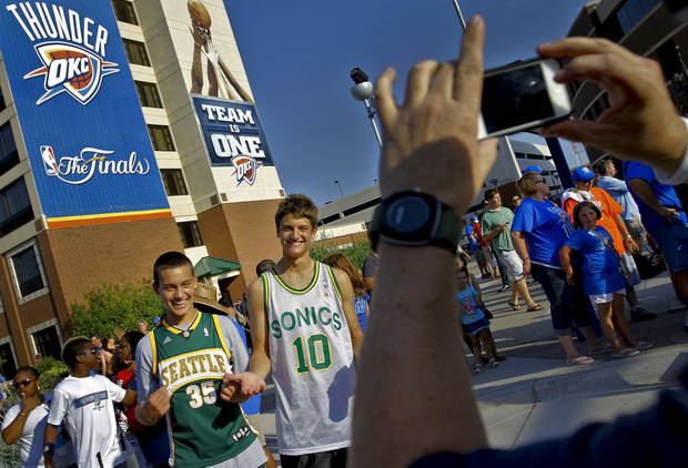 An Oklahoma City Thunder fan takes a photo of Peter and Alec Ernst who wear Seattle Supersonics's jerseys while walking in Thunder Alley during Game 2 of the NBA Finals between the Oklahoma City Thunder and the Miami Heat at Chesapeake Energy Arena in Oklahoma City, Thursday, June 14, 2012. Photo by Chris Landsberger, The Oklahoman