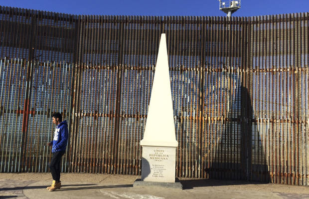 "Brandon Azul, 17, walks away from a monument marking Mexico's border with the United States in Tijuana, Mexico, Wednesday, Jan. 25, 2017. President Donald Trump moved aggressively to tighten the nation's immigration controls Wednesday, signing executive actions to jumpstart construction of his promised U.S.-Mexico border wall and cut federal grants for immigrant-protecting ""sanctuary cities."" (AP Photo/Julie Watson)"