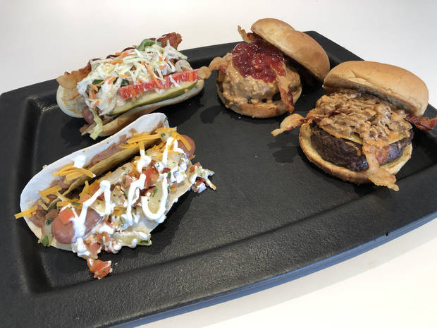 The Oklahoma City Dodgers will offer new food items such as the Taco Dog, front left, the Gouda Burger, front right, the Southern Comfort Dog, back left, and the PB&J Burger, back right, this season. [Photo by Jacob Unruh/The Oklahoman]