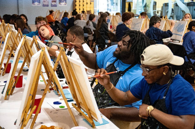 Rose State College students participate in a painting event at the campus's wellness center.
