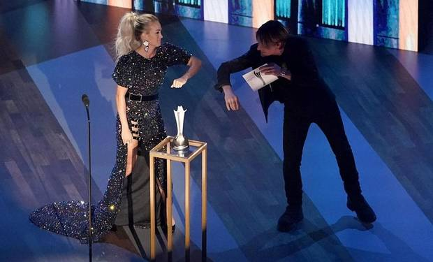 Carrie Underwood, left, winner of the entertainer of the year award, elbow bumps host Keith Urban on stage during the 55th annual Academy of Country Music Awards at the Grand Ole Opry House on Wednesday, Sept. 16, 2020, in Nashville, Tenn. [AP Photo/Mark Humphrey]