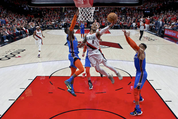 Portland Trail Blazers guard Damian Lillard, center, shoots between Oklahoma City Thunder guard Dennis Schroeder, left, and guard Russell Westbrook, right, during the second half of Game 2 of an NBA basketball first-round playoff series Tuesday, April 16, 2019, in Portland, Ore. The Trail Blazers won 114-94. (AP Photo/Craig Mitchelldyer)
