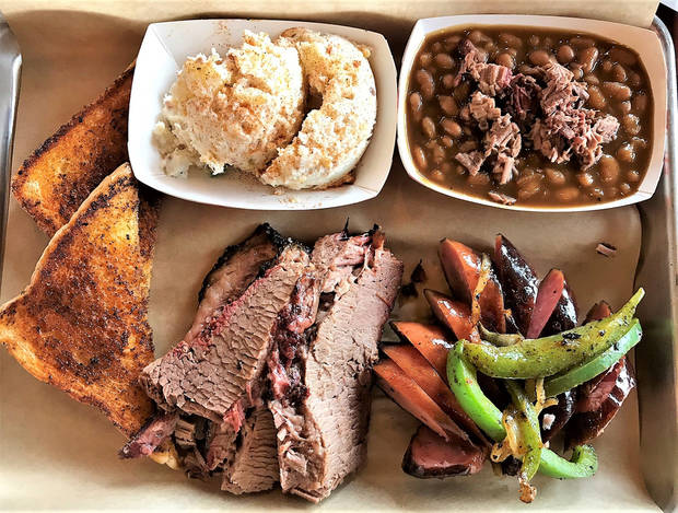 Sliced brisket plus smoked sausage with onions and peppers, potato salad and barbecue baked beans from Cornish Smokehouse. [Dave Cathey/The Oklahoman]
