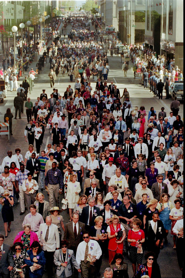 Friends, family and survivors of the bombing of the Alfred P. Murrah federal building walk through the streets of Oklahoma City during the anniversary remembrance, Friday, April 19, 1996. (AP Photo/Brandi Stafford/Pool/Tulsa World)