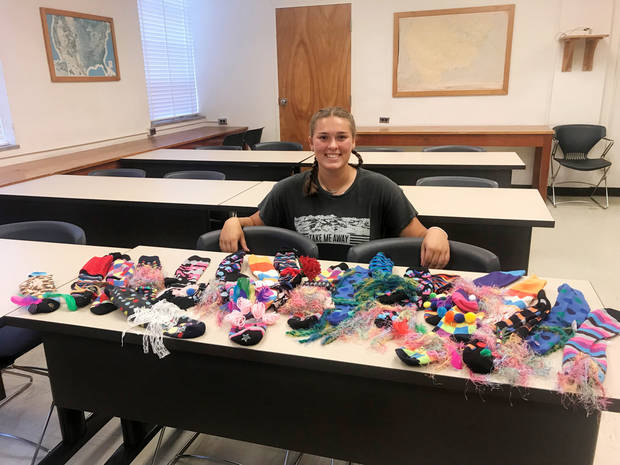 Taelor Brown, Pawnee County 4-H president, displays all the crazy sock puppets made at the workshop she led at the State 4-H Roundup in July. [PHOTO PROVIDED]