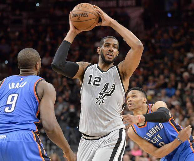 San Antonio Spurs forward LaMarcus Aldridge (12) looks to pass as he is defended by Oklahoma City Thunder forward Serge Ibaka (9) and Thunder guard Russell Westbrook during the second half of an NBA basketball game, Saturday, March 12, 2016, in San Antonio. San Antonio won 93-85. (AP Photo/Darren Abate)
