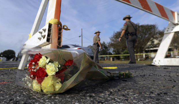 A bouquet of flowers lies at the base of a roadblock where law enforcement officials work at the scene of a shooting at the First Baptist Church of Sutherland Springs, Monday, Nov. 6, 2017, in Sutherland Springs, Texas. A man opened fire inside the church in the small South Texas community on Sunday, killing and wounding many. (AP Photo/Eric Gay)