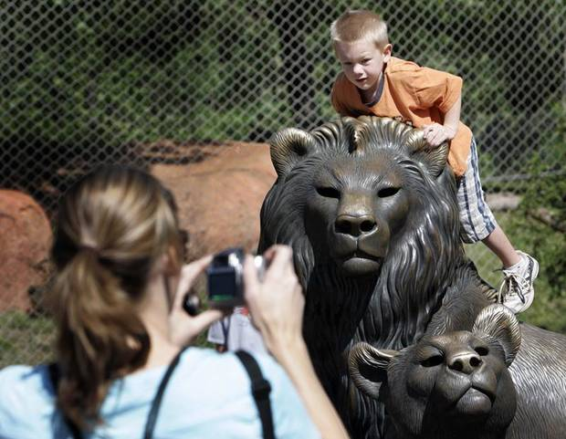 Kim Christensen take a photo of her son Stoddard, 5, on the lion statue  at the Oklahoma City Zoo, Wednesday, May 20, 2009. Photo By David McDaniel, The Oklahoman.